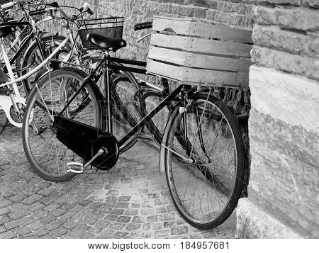 Bicycles leaning against a wall. The first bicycle has a wooden box instead a bicycle basket.