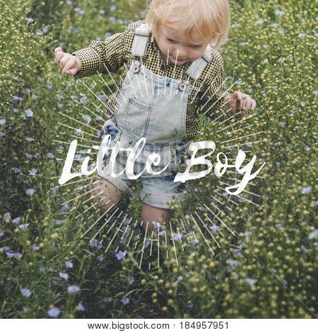 Little blonde boy walking in the meadows