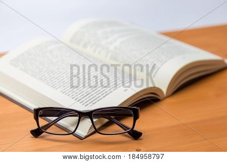 Open Thick Book With Glasses In Front Of It On A Wood Desk