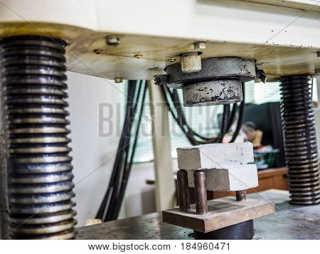physical testing machine in engineering laboratory with load cell to calculated compressive strenght or tensile and flextural property