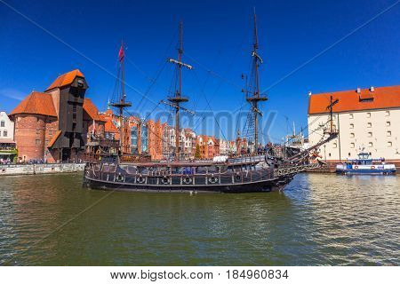 GDANSK, POLAND - MAY 2, 2017: Pirate ship at the Motlawa river in Gdansk. Port crane in Gdansk built between 1442 and 1444 is the city symbol and the oldest surviving port crane in Europe.
