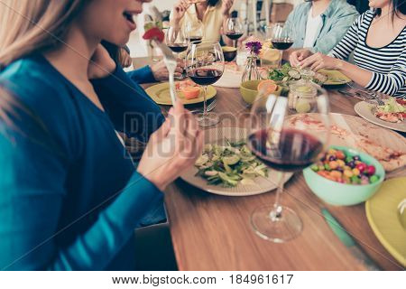 Close up of girl eating salad at the party. Table is full of dishes and glasses of wine. Friends are having fun and enjoying