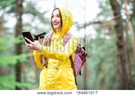 Young woman in yellow raincoat using smart phone for orientation during the walk in the green pine forest