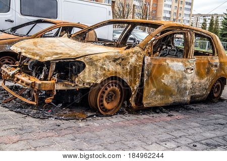 Burnt car is on the asphalt road