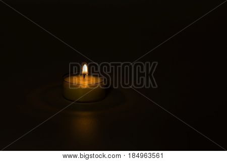 Small lit candle with soft light isolated on dark background