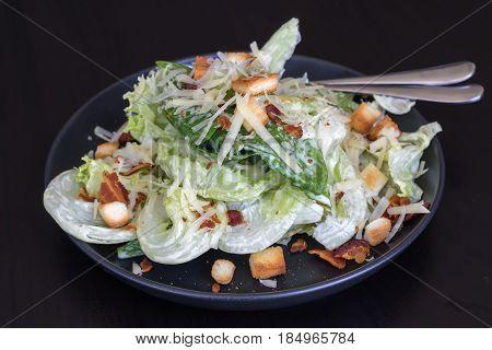 Cesar salad in black dish on black background