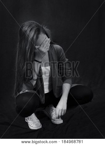 Monochrome close up portrait of young beautiful girl sitting and closing her face