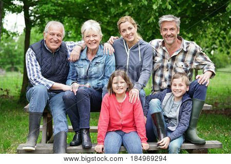 Portrait of happy family sitting on picnic table in private property
