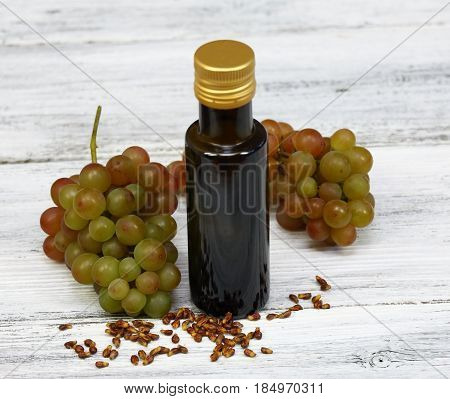 Grape seed oil grape seeds in front fresh grapes around