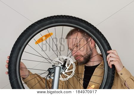 Bearded Man Checks The Fastening Of The Front Wheel.