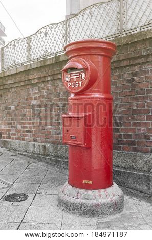 Old Japanese postbox stands beside a street in front of brick wall in a city of Japan (with Japanese language translated as Post)