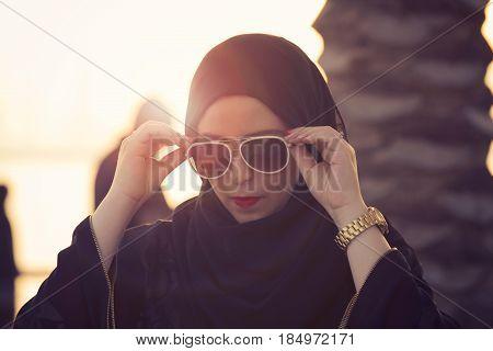 Arab woman wearing black sunglasses - Dubai sunrise time