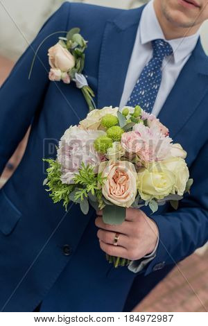 Bouquet in the hands of groom.