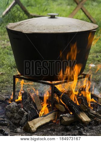 Food in a big cauldron on a fire. Cooking outdoors in cast-iron cauldron.