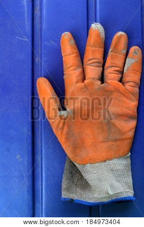 dirty used orange garden gloves on top lay