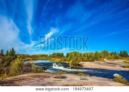 On the shore is a wooden bench for tourists. Thin flying cirrus clouds over broad Winnipeg River, Old Pinawa Dam Park. The concept of ecological  tourism