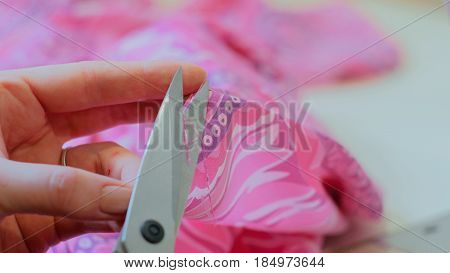 Professional dressmaker, tailor cutting a piece of cloth in her workshop. Fashion and tailoring concept