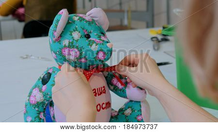 Tailor woman, toymaker tying bow on neck of teddy bear at sewing studio. Handmade, craft and toy making concept. Close up shot