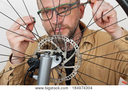 Bearded Man Screws The Front Wheel On The Mtb Bicycle.