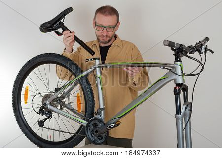 Bearded Caucasian Man Putting A Saddle On The Mtb Bicycle