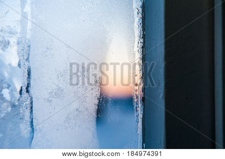 Frost patterns on window. Festive bokeh background white glass texture.