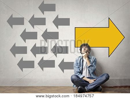 Guy sitting on the floor thinking of possible alternatives