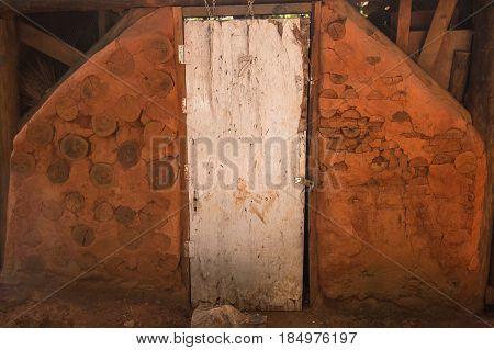 Rustic Adobe Wall with wooden door. Brazil