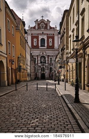 The cobbled street and the facade of the baroque church in Poznan