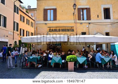 ROME ITALY - APRIL 12 2017: People eating traditional italian food in outdoor restaurant Carlo Menta in Trastevere district in Rome Italy on April 12 2017.