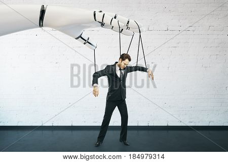 Robotic hand manipulating businessman on brick background. Future concept