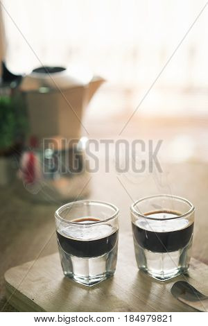 two espresso cup on the wood table with morning vintage tone espresso coffee pot in blur background.