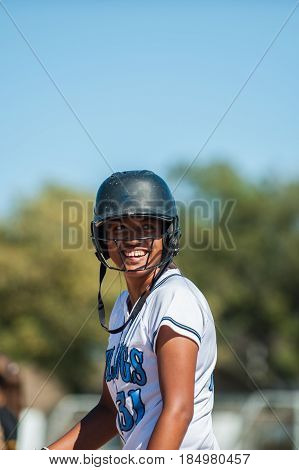 Smiling Filipino softball player in white uniform.