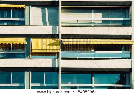 Row of Balconies with awning opened - covered by sun-shield on a warm summer day