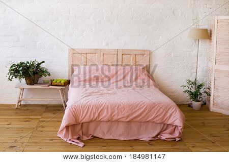 Empty bed with pink pillows and pink cover in the bedroom. White wall wooden floor home flowers with green leaves floor lamp and small table near the bed apples and the book on it. Home interior