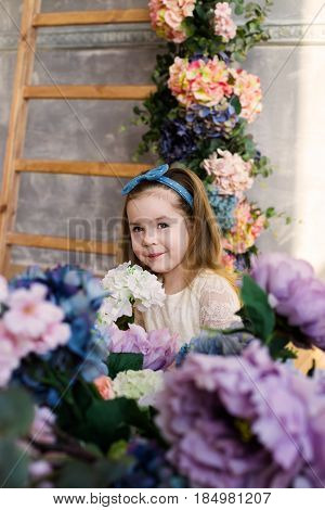 Beautiful little girl posing with a large bouquet of flowers in a white lacy dress at home. Wooden stairs decorated with colorful flowers on the background