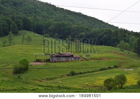 Mountain farm nestled in a grass and tree setting.