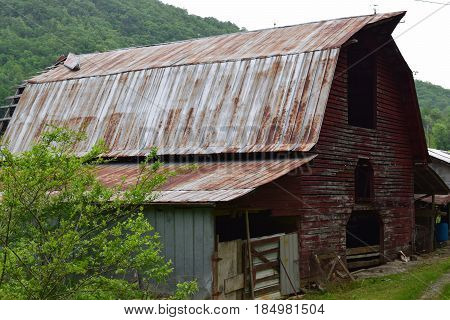 Large red barn in a mountain setting