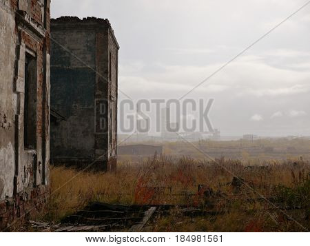 ruins of abandoned building in tundra with coalmine in the background