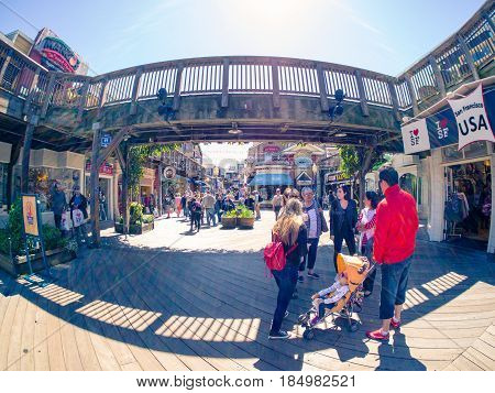 San Francisco, CA, USA - April 3, 2017: Touring family with child in carriage standing under the wooden bridge at Pier 39, Fisherman's Wharf