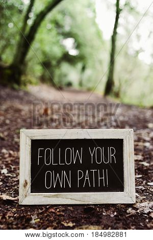 closeup of a wooden-framed chalkboard with the text follow your own path written in it, placed on the ground in a path in the forest