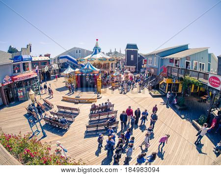 San Francisco, CA, USA - April 3, 2017: Groups of tourists with children standing near the carousel at the Pier 39, Fisherman's Wharf