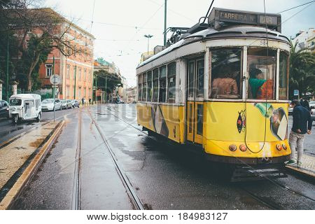 LISBON, PORTUGAL - February 2017:Famous yellow tram 28 line on station in front of Basilica Estrella,public transport that is attractions of Lisbon and Portugal