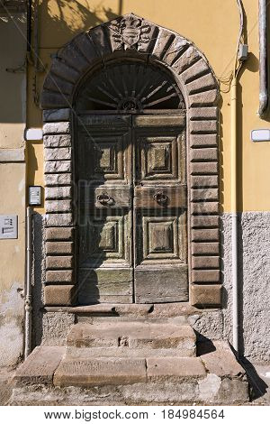 Old wooden door in the ancient and small town of Lucca Toscana (Tuscany) Italy Europe