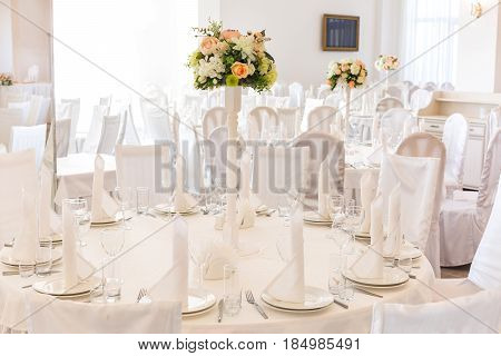 Festive table setting in classic style in a white restaurant interior, setout. Wedding table decor concept. Fine art. Expectation of guests.