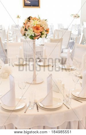 Festive table setting in classic style in a white restaurant interior, setout. Wedding table decor concept. Fine art. Expectation of guests. Verical.