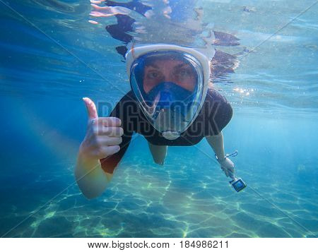 Snorkeling woman with thumb up and action camera. Snorkeling gear undersea photo. Snorkel in full face mask. Pretty girl in water. Underwater swimming in ocean. Tropical vacation activity snorkeling