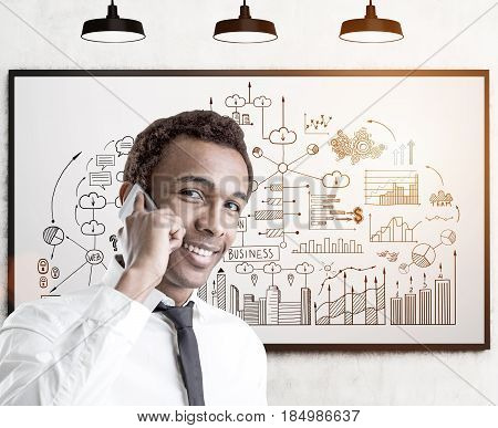 Portrait of a young smiling African American businessman with a smartphone standing near a whiteboard with a business scheme on it. Toned image