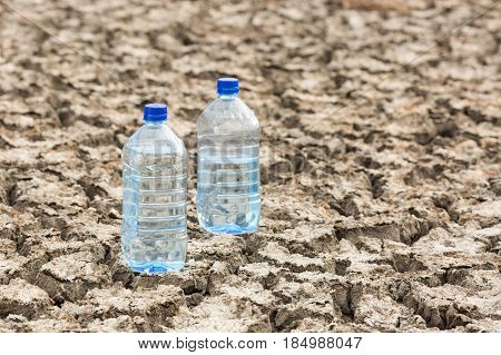 Bottle with water on the dried ground. Concept of Global drought, warming, summer. Dried soil. lack of water, thirst concept.