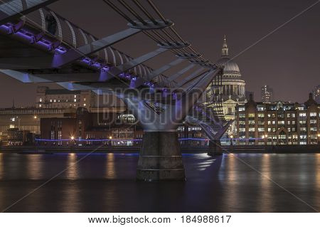 Illuminated on purple Millenium Bridge in the background Cathedral of Sts. Paul