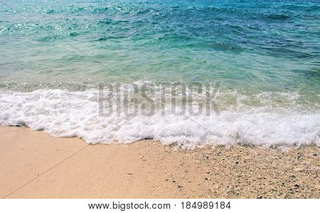Oceanic wave over white sand beach. Marine scene with sand beach and sea wave. Clean blue tropical sea lagoon for perfect vacation. Summer holiday banner template. Tropic seaside photo for background